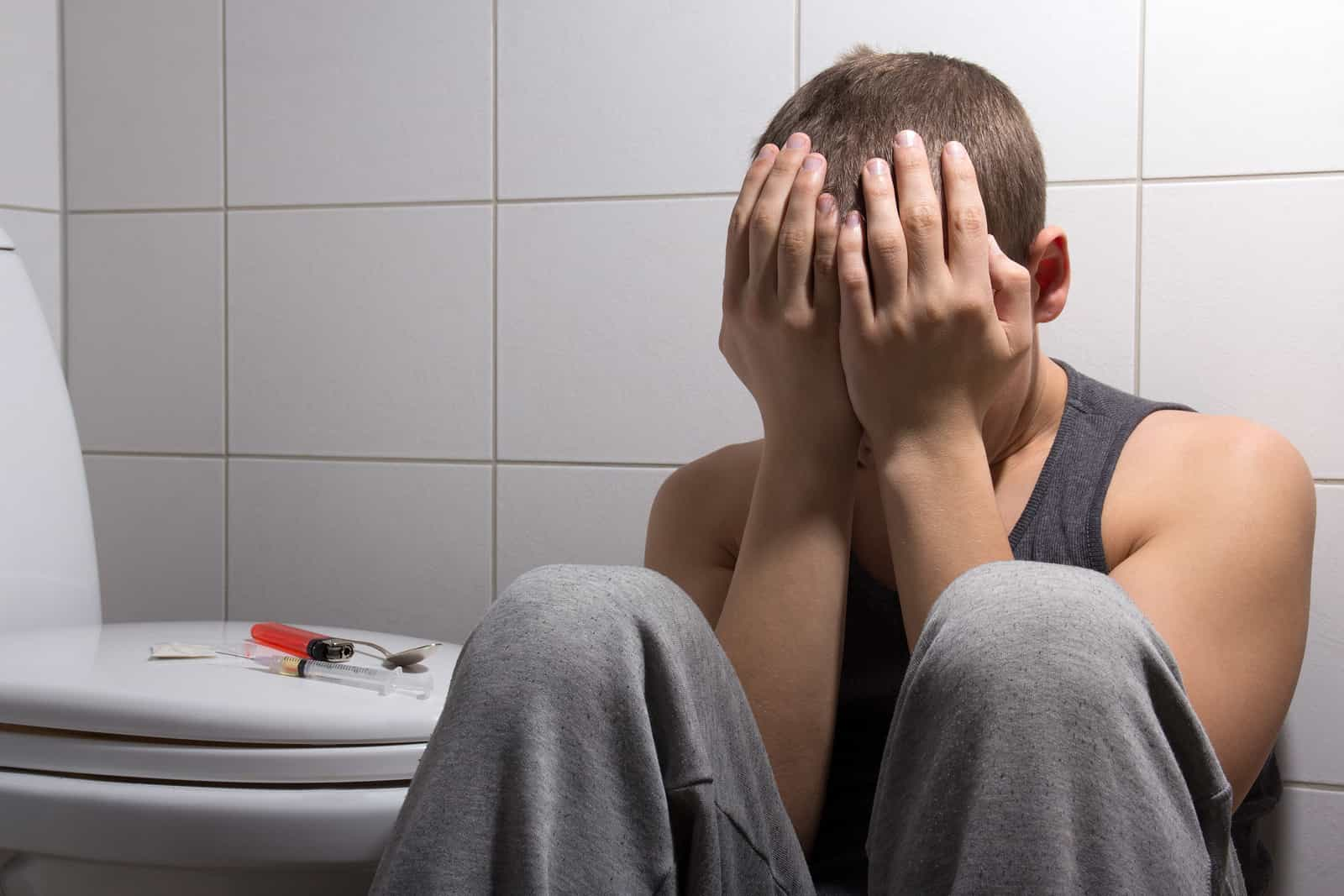 Stoned Man With Heroin Addiction Sitting In Bathroom