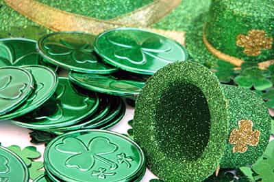 shot of several green coins with a shamrock on it. a green hat with a shamrock is laying next to the coins. over white.