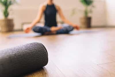 Close up of rolled yoga mat in fitness center and blurred woman at the back in lotus yoga pose.