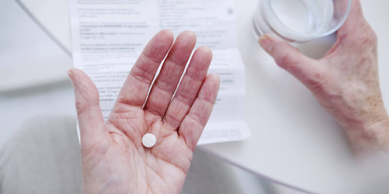 Elderly hands holding medication tablet